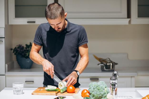 Красивый мужчина готовит завтрак на кухне | Бесплатно Фото